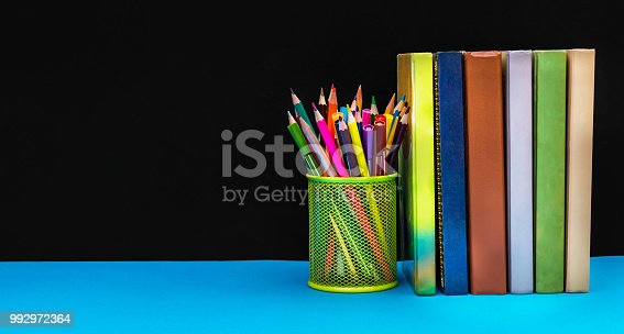 istock Holder with colored pencils and row of books against blackboard. Space for text. School concept. 992972364