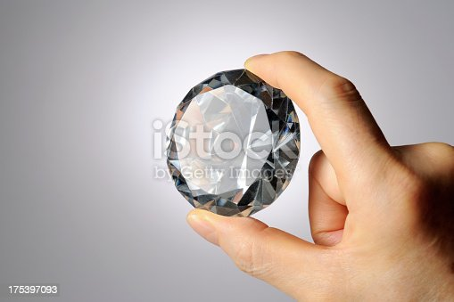 Close-up shot of holding a big diamond against gray gradation background.