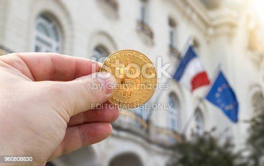 Vienna Austria May.3 2018, Hand holding golden Bitcoin against flags of France and European Union, concept
