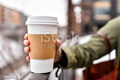 Holding a blank coffee cup with a out of focus city background. Photo taken in the winter in Minneapolis, Minnesota.