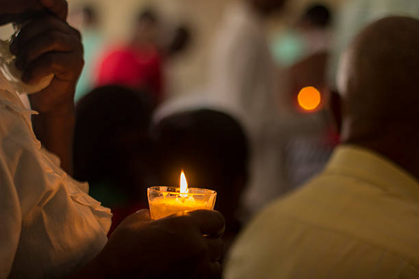 Holding a candle during Mass stock photo