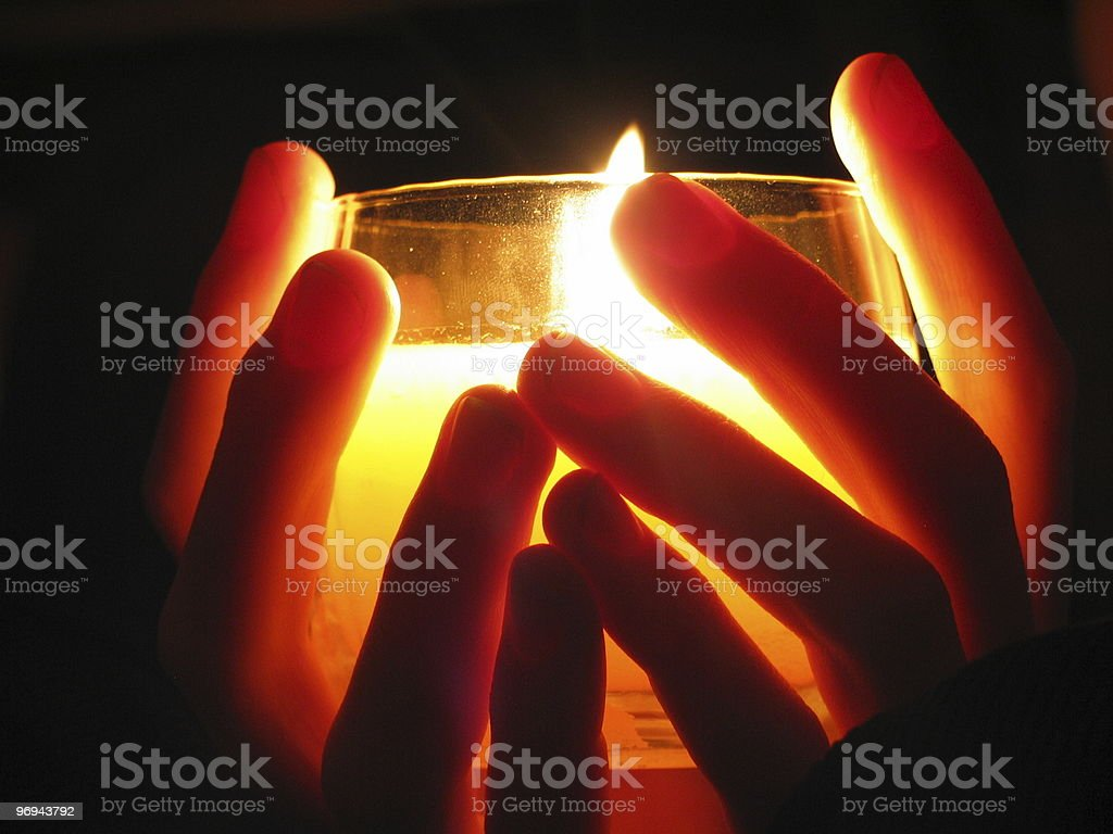 holding a candle in darkness stock photo