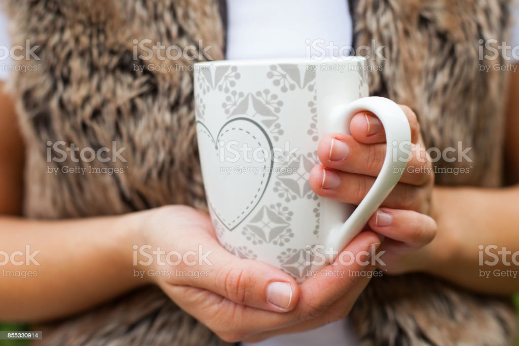 Holding a cup of coffee - closeup stock photo