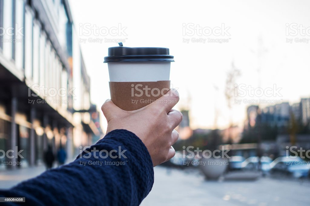 holding a disposable cup of coffee stock photo