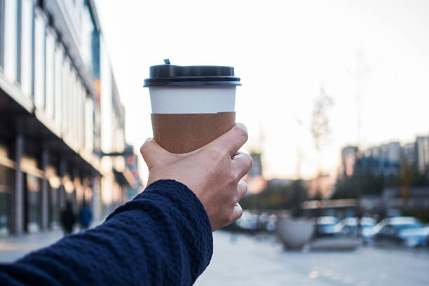 holding a disposable cup of coffee - paper coffee cup stock photos and pictures
