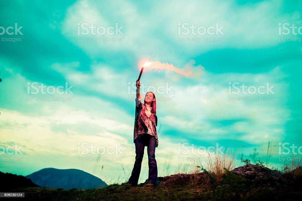 Holding a flaming torch on mountain stock photo