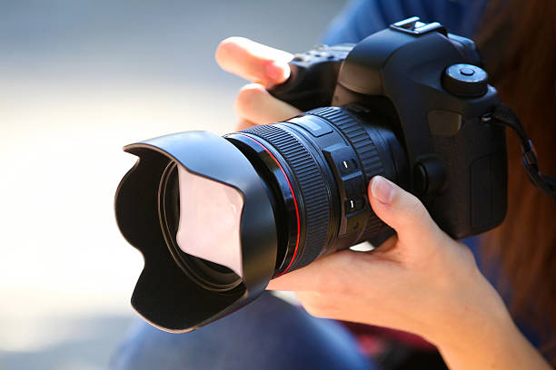 holding a full frame camera. - photography themes stock photos and pictures