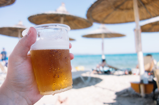 Holding a glass of beer on beach