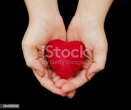 A woman's hands holding a small felted heart (made by me).  Isolated on black.