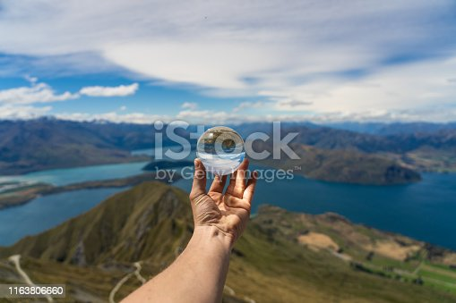 istock holding a lens ball at the top of Roys peak in New Zealand, crystal ball on the top of a mountain in New Zealand, Roys peak image, lens ball photography 1163806660