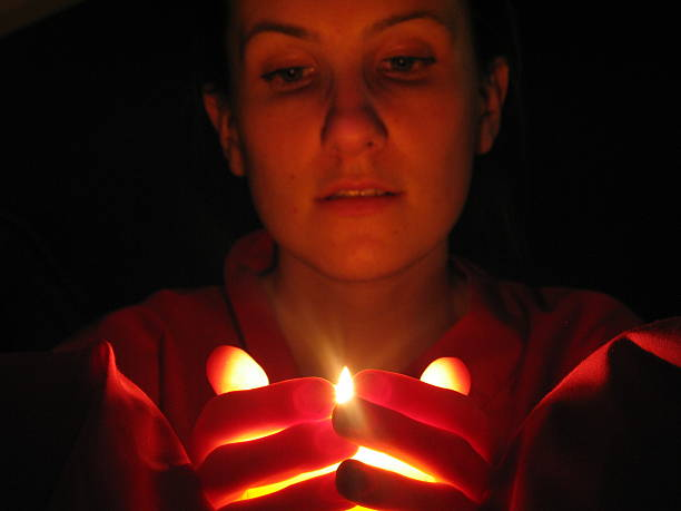 holding a light and watching flame of a candle stock photo