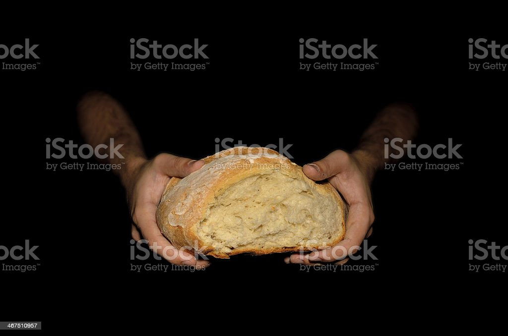 Holding a Loaf of Bread on Dark Background stock photo