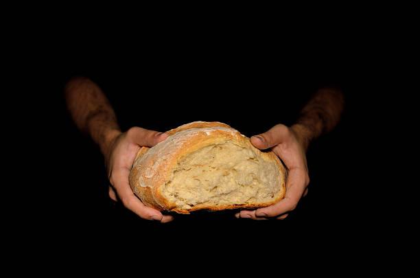 Hält sich einen Laib Brot auf dunklem Hintergrund – Foto