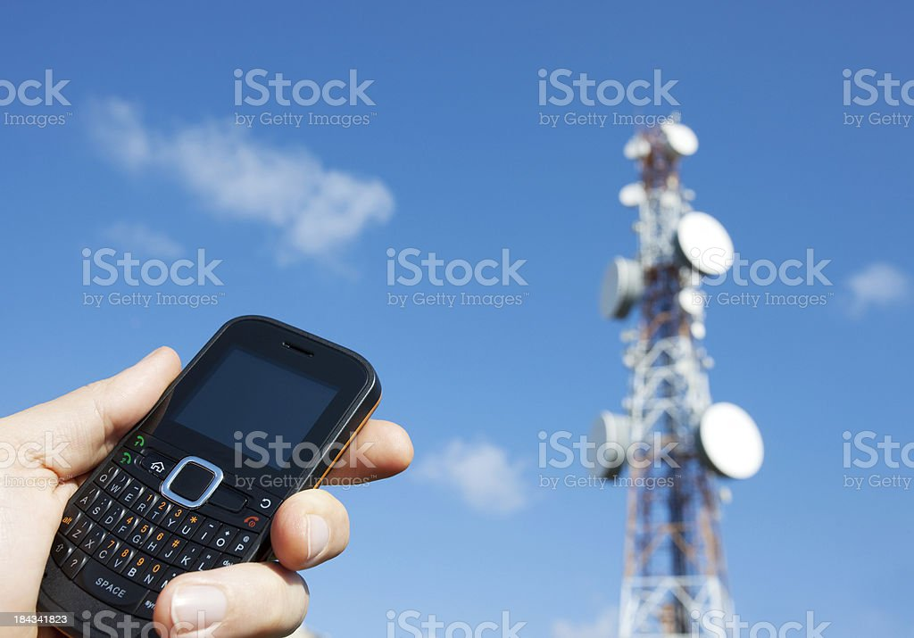Holding a mobile phone and communication tower royalty-free stock photo