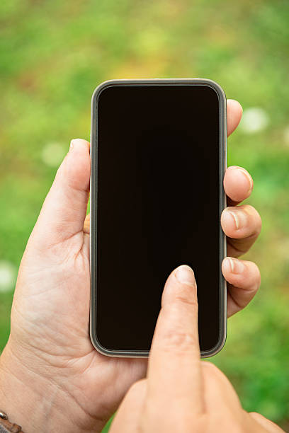 holding a new smartphone outdoors stock photo
