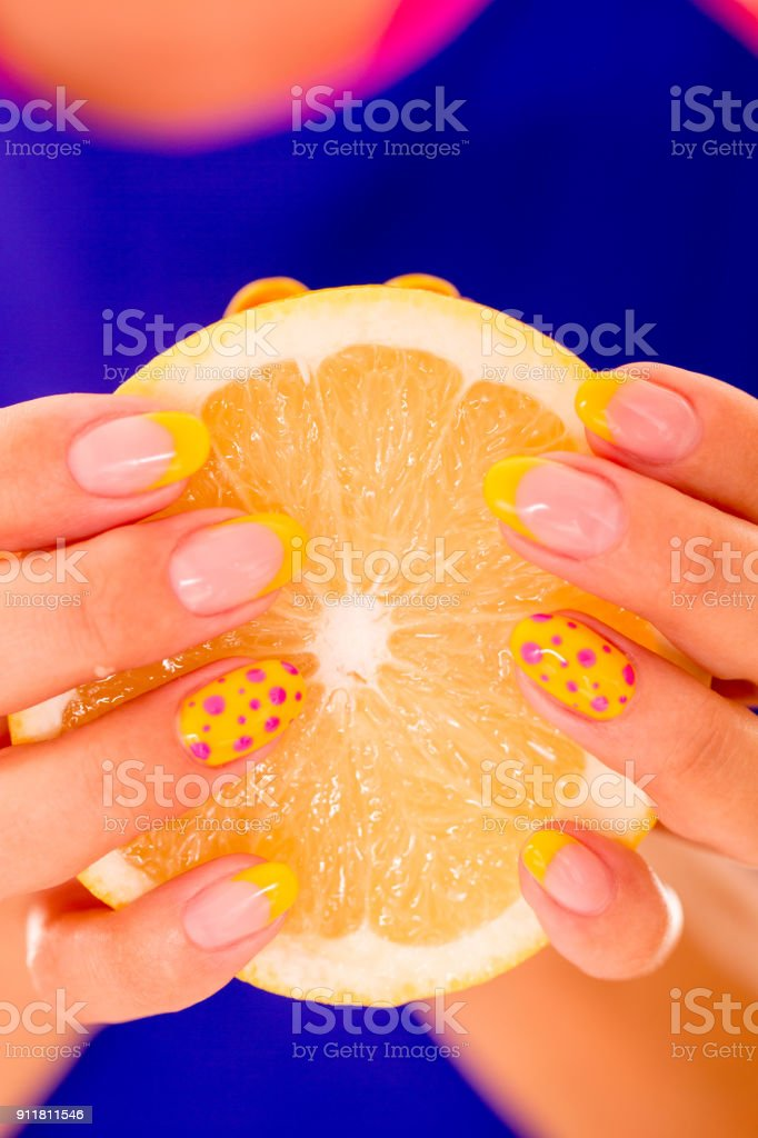 Woman Holding a Peice of Sliced Orange with Polished Nails on Blue...