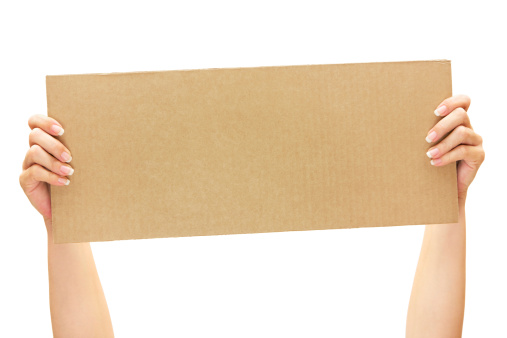 Woman showing a blank piece of brown cardboard. Isolated on a white background.