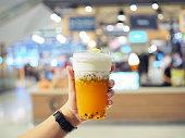 クリーム チーズの泡の層でアイス パッション フルーツ ティーのプラスチック ガラスを保持しています。トレンディな中国飲料。