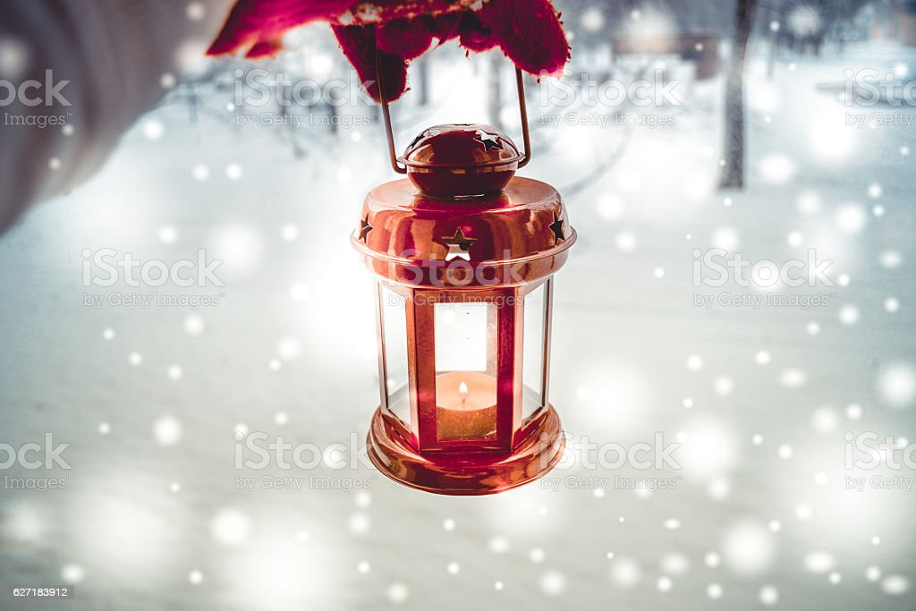 Holding a red candle lantern in the winter forest. stock photo