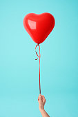 Holding a red heart shape balloon against blue background