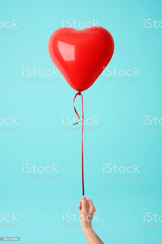 Holding a red heart shape balloon against blue background stock photo