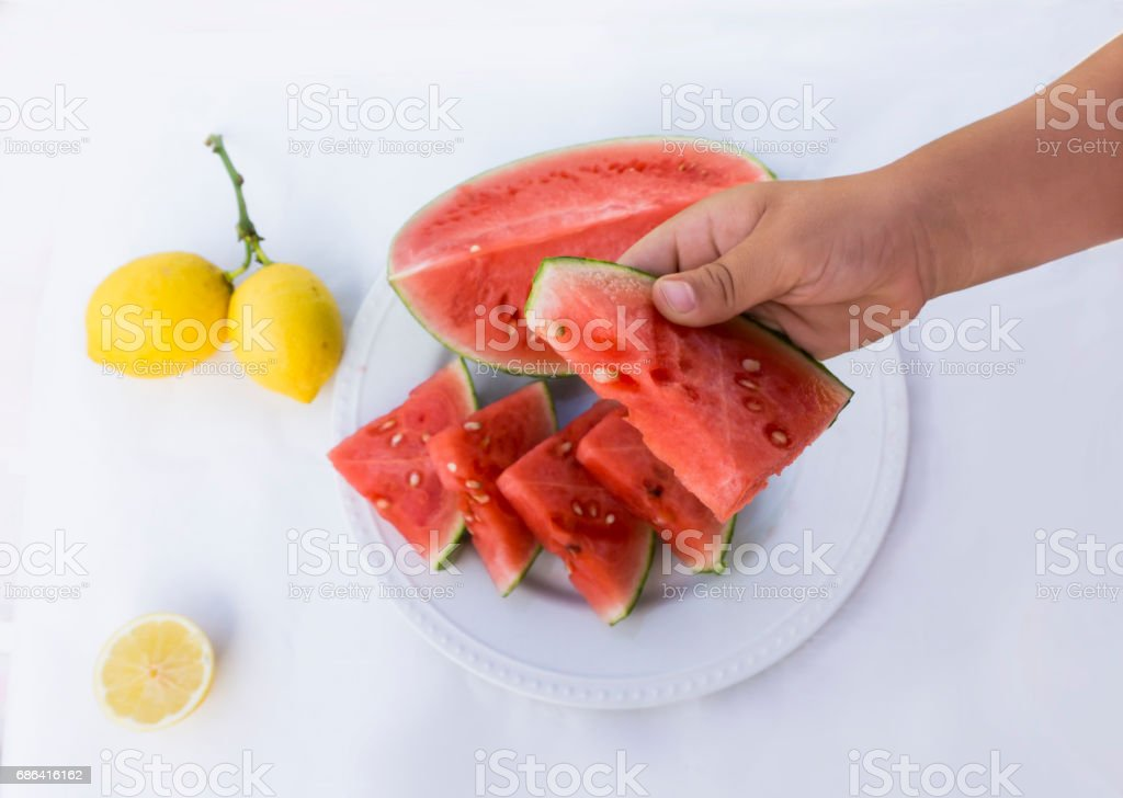 Holding a slice of watermelon stock photo
