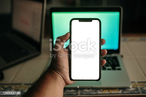 Holding a smart phone with blank screen by a laptop