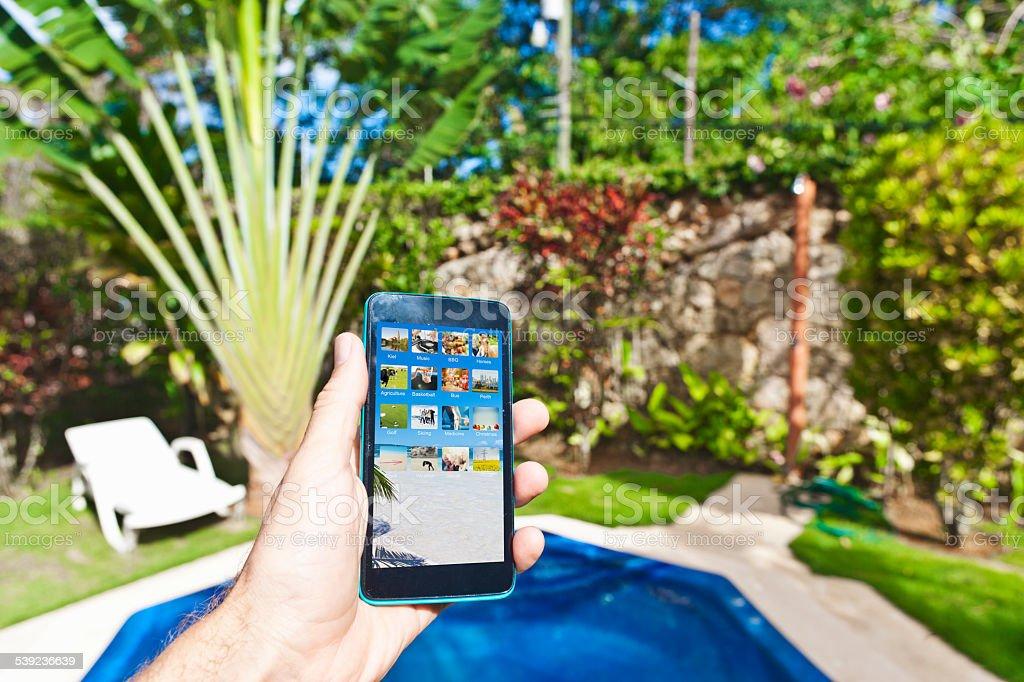 Sosteniendo un teléfono inteligente en jardín caribeña de la República Dominicana foto de stock libre de derechos