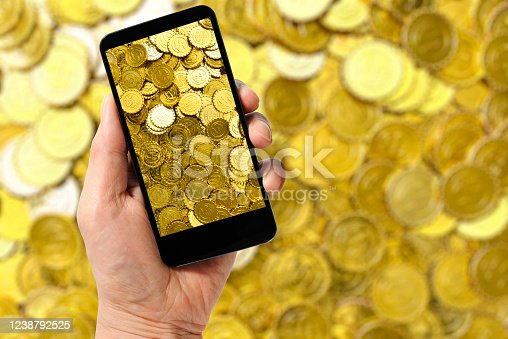 Holding a smartphone with gold coins against a lot of gold coins.