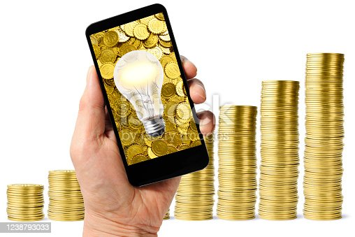 Holding a smartphone with illuminated light bulb against stair-shaped gold coins.