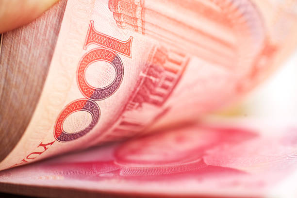 Holding a stack of chinese mone Details of a stack of one hundred yuan notes .Chinese currency. chinese currency stock pictures, royalty-free photos & images