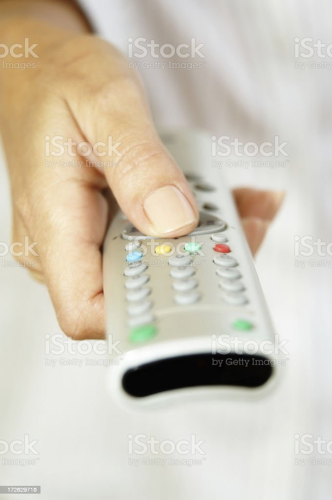 Holding a TV remote control royalty-free stock photo