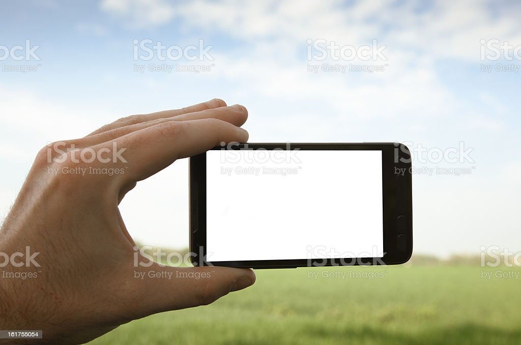 Holding a white mobile smart phone outdoors royalty-free stock photo