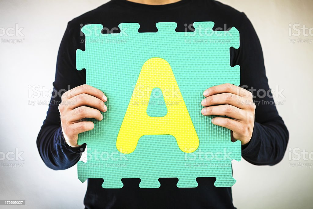Holding Alphabet Puzzle, Letter A royalty-free stock photo