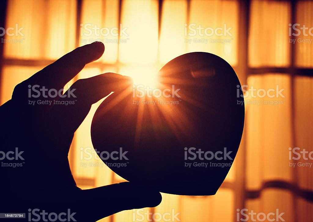 Holding an heart shape silhouette royalty-free stock photo