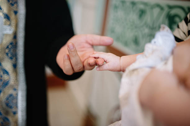holding baby hand during christening stock photo
