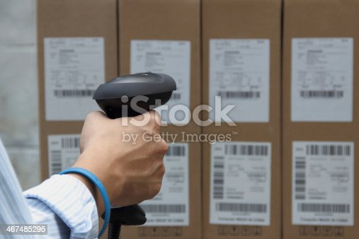 92884259 istock photo Holding barcode scanner with a label on the boxes 467485295