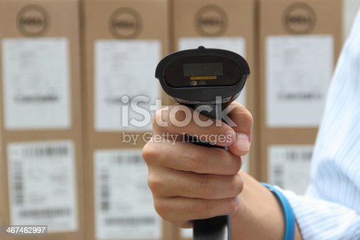 92884259 istock photo Holding barcode scanner with label on the boxes background 467462997
