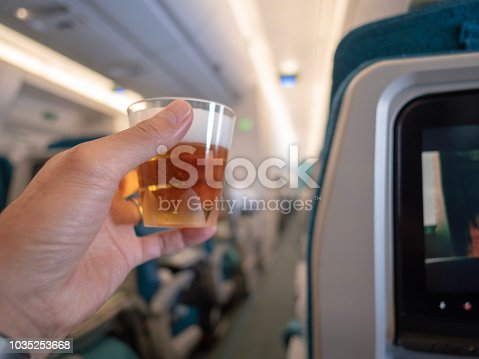 istock Holding beer glass in airplane 1035253668