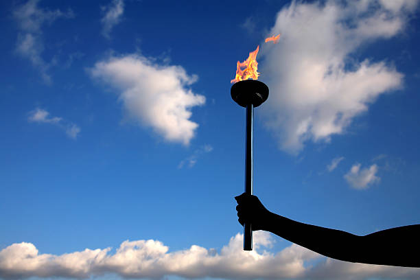 holding burning flaming torch silhouetted hand holding a burning flaming torch over cloudy sky.  flaming torch stock pictures, royalty-free photos & images