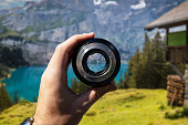 Holding camera lens in hand focus view of landscape with blue lake and bungalow