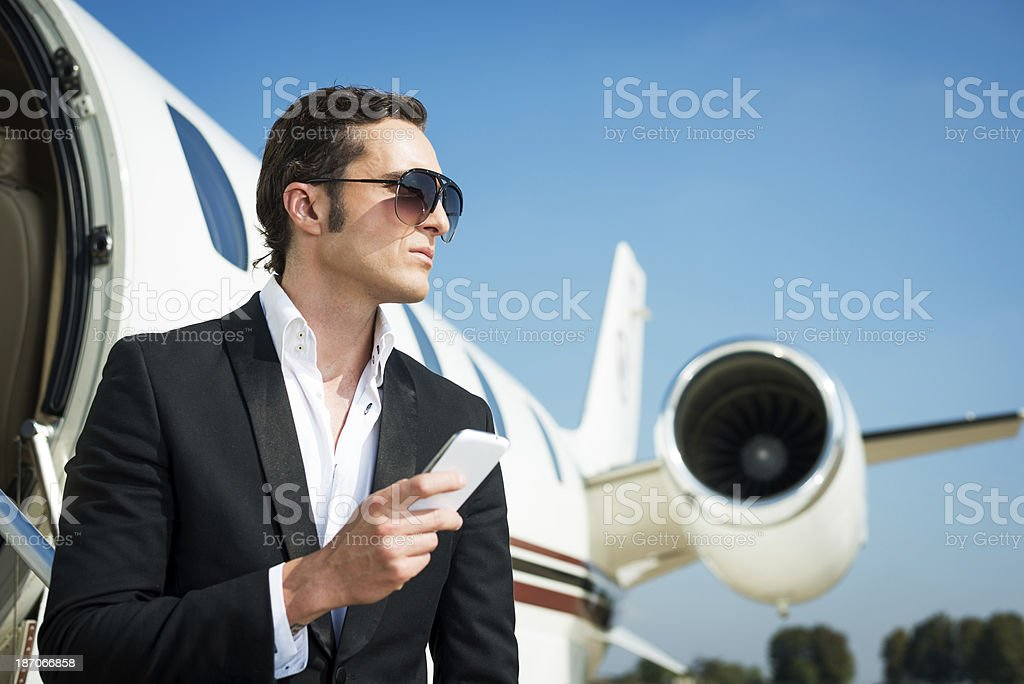 CEO holding cell phone in front of private jet royalty-free stock photo