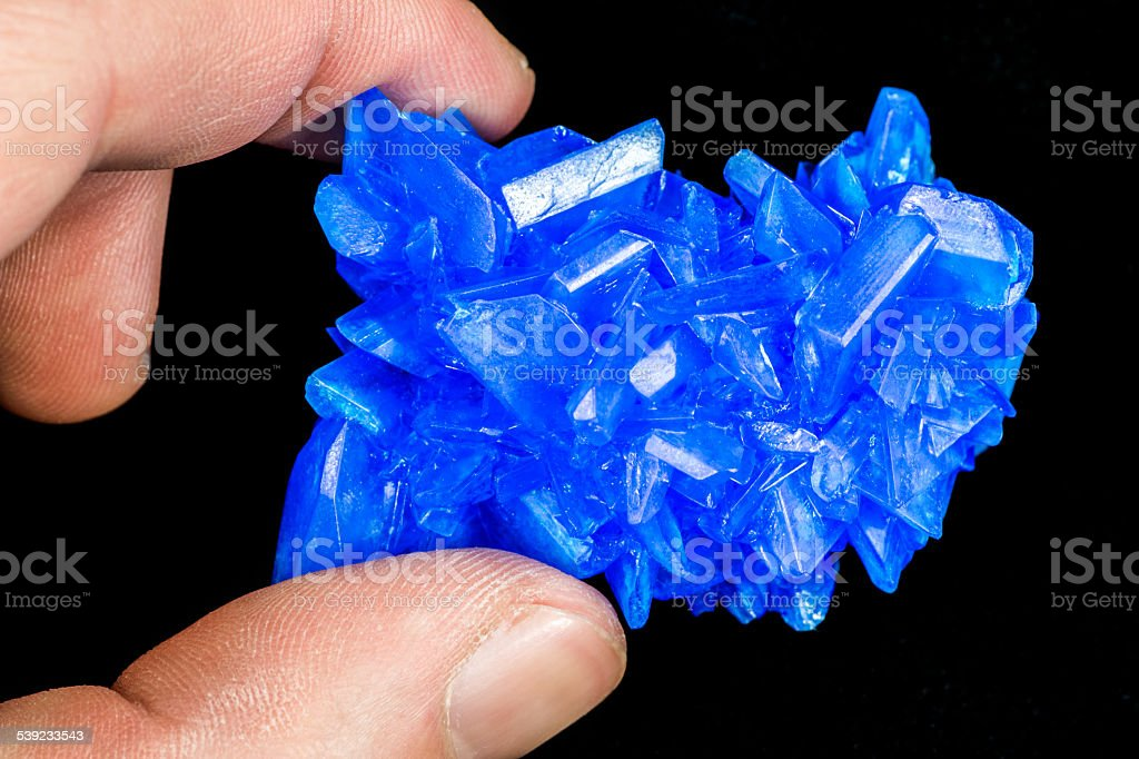 Holding Chalcanthite blue stone copper sulfate crystals on black royalty-free stock photo