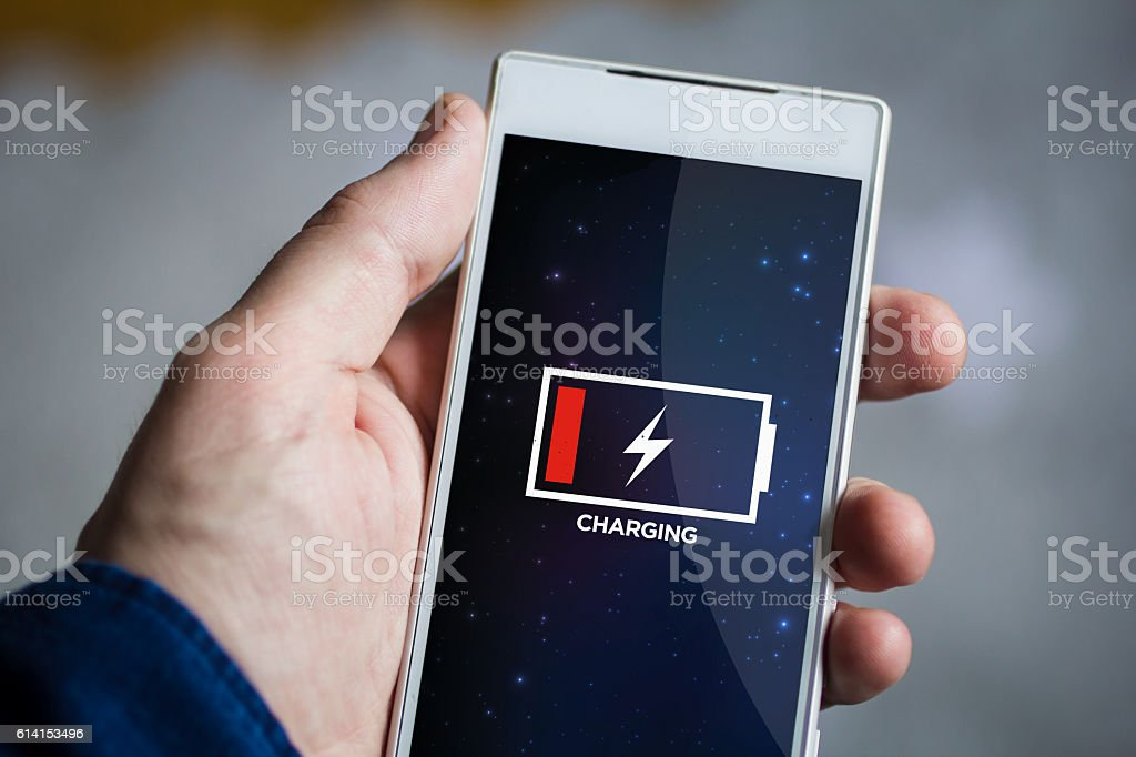 holding charging smartphone stock photo