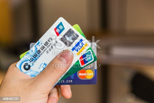 Shanghai, China - Nov 20, 2013: Man holding credit cards. UnionPay, Visa and Mastercard are the three most commonly used cards in China.