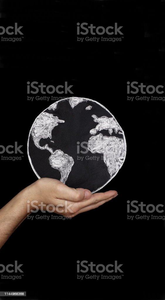 Holding earth front of black blackboard