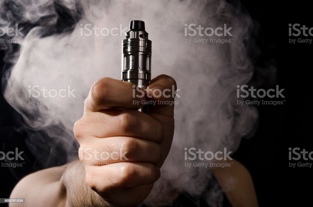 holding electronic cigarette with smoke behind. stock photo