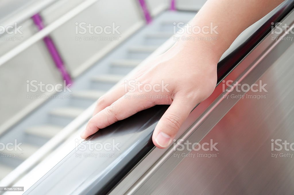 Holding escalator handrail stock photo