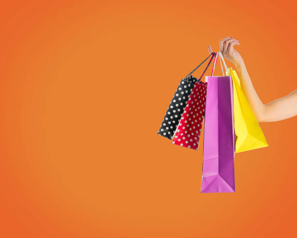 Holding fancy shopping bags on orange background stock photo