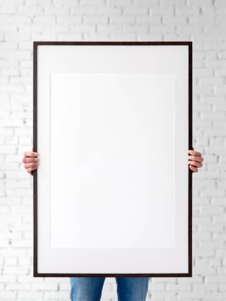 Holding Frame Mockup. Foto Mockup. Der Mann hält Rahmen. Für Rahmen und Plakate Design. Rahmengröße 24x36 (61x91cm). – Foto